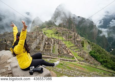 Asian Woman Traveler Raising Hand At Machu Picchu, One Of Seven Wonders And Famous Tourist Attractio