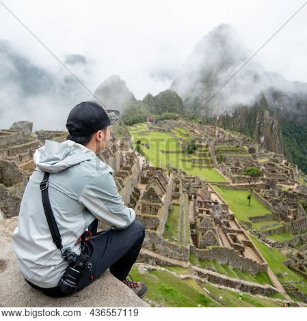 Young Asian Man Traveler And Photographer Looking At Machu Picchu, One Of Seven Wonders And Famous T