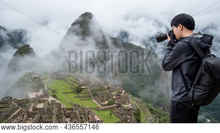 Asian Man Traveler And Photographer Taking Photo At Machu Picchu, One Of Seven Wonders And Famous To