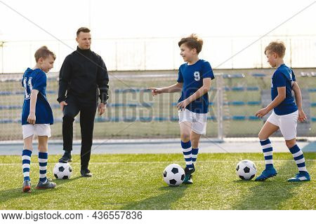 Happy Boys Talking With Junior Coach On Training Unit. Coach Coaching Kids On Football Field. Young