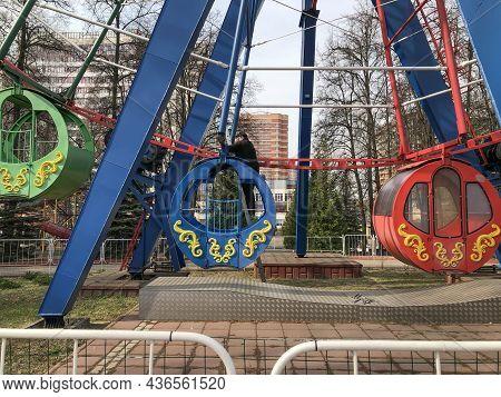 Vidnoe, Russia - April 15, 2021: Repairing Carousels In A City Park, Repairman Repairing A Ferris Wh