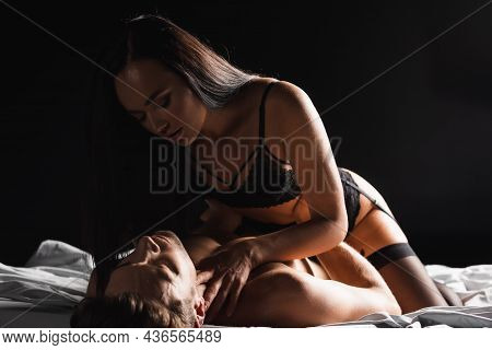 Passionate Woman In Lingerie And Garter Belt Touching Muscular Boyfriend On Bed Isolated On Black