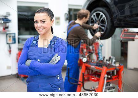 Female Mechanic Standing In A Garage