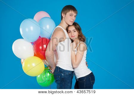 Smiling Young Love Couple Holding Diversicolored Balloons