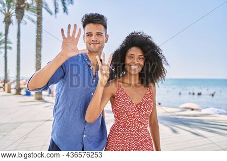 Young interracial couple outdoors on a sunny day showing and pointing up with fingers number eight while smiling confident and happy.