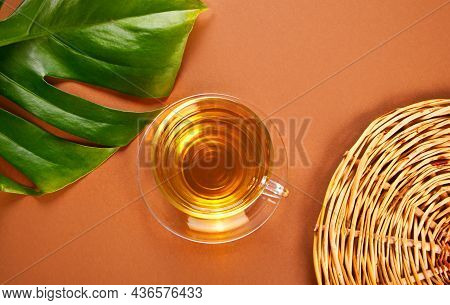 Refreshing Green Or Black Tea With Palm Leaf On The Brawn Background