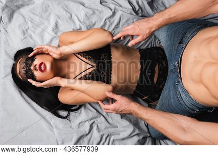 Top View Of Sensual Woman In Lingerie And Lace Mask Lying Near Muscular Boyfriend On Bed
