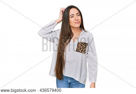 Young hispanic girl wearing casual clothes confuse and wonder about question. uncertain with doubt, thinking with hand on head. pensive concept.