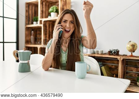 Young hispanic woman talking on the smartphone sitting on the table at home annoyed and frustrated shouting with anger, yelling crazy with anger and hand raised
