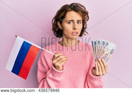 Young brunette woman holding russia flag and rubles banknotes clueless and confused expression. doubt concept.