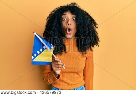 African american woman with afro hair holding bosnia herzegovina flag scared and amazed with open mouth for surprise, disbelief face