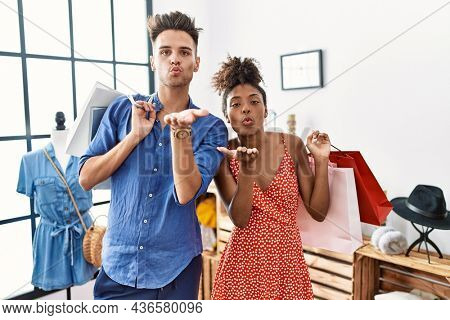 Young interracial couple holding shopping bags at retail shop looking at the camera blowing a kiss with hand on air being lovely and sexy. love expression.