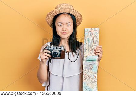 Young chinese girl holding city map and vintage camera skeptic and nervous, frowning upset because of problem. negative person.