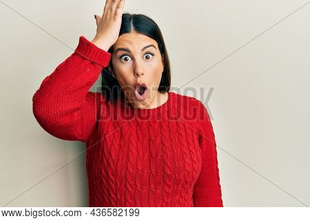 Beautiful brunette woman wearing wool winter sweater surprised with hand on head for mistake, remember error. forgot, bad memory concept.