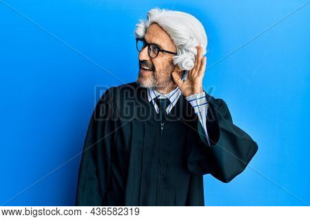 Middle age hispanic man wearing judge uniform smiling with hand over ear listening and hearing to rumor or gossip. deafness concept.