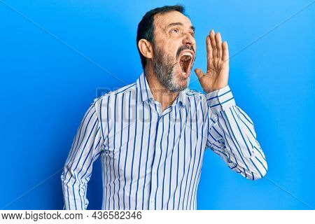 Middle age hispanic man wearing casual clothes shouting and screaming loud to side with hand on mouth. communication concept.