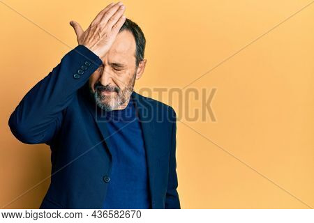 Middle age hispanic man wearing business clothes surprised with hand on head for mistake, remember error. forgot, bad memory concept.