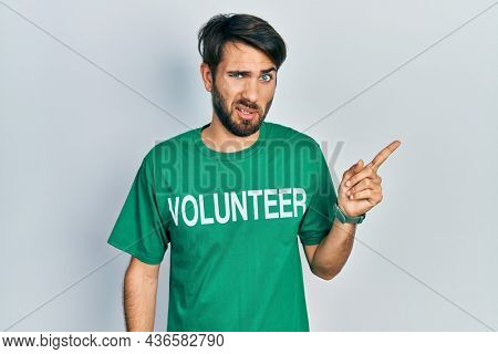 Young hispanic man wearing volunteer t shirt pointing aside worried and nervous with forefinger, concerned and surprised expression