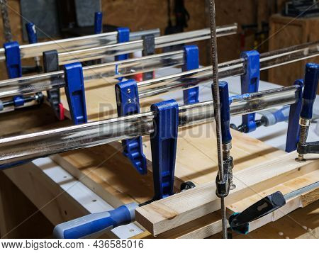 Glued Alder Wood Boards On Workbench, Focus On The Blue Clamp In A Small Woodworking Shop.