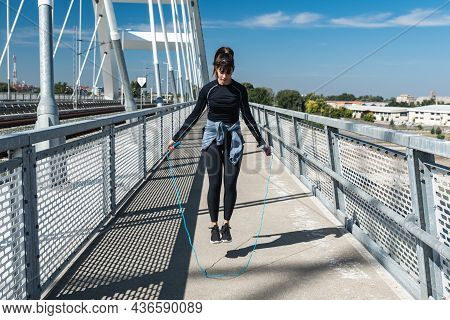 Horizontal Shot Of Young Muscular Woman With Skipping Rope Outdoors. Fitness Female Doing Skipping W