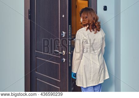 Woman Doctor Enters The Apartment When Visiting A Patient Home.