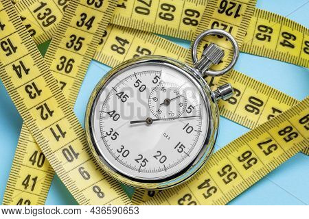 Fitness Workout For Weight Loss. Measuring Tape And Stopwatch On A Blue Background