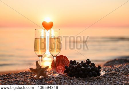 Romantic Atmosphere At Sunset By The Sea. Heart Between Glasses Against The Background Of The Sun. S