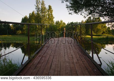 Woman On The Wooden Bridge In Sunset Light. The Footbridge Over The River Has Wooden Deck And Metal