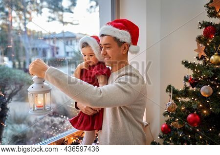 christmas, winter holidays and family concept - happy middle-aged father with lantern and baby daughter at window at home
