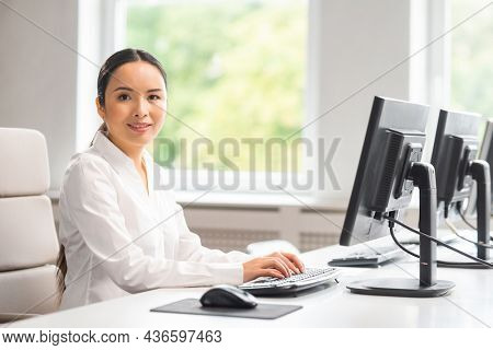 Asian business woman is working at her table in a modern office. The workplace of a successful specialist. Business, confidence and finance.