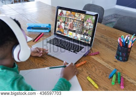 African american boy using laptop for video call, with diverse elementary school pupils on screen. communication technology and online education, digital composite image.
