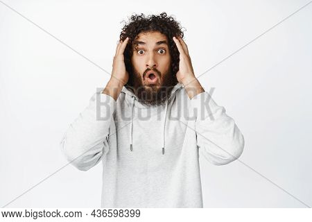 Image Of Shocked And Overwhelmed Hispanic Man, Staring In Awe At Camera, Holding Hands On Head In Pa
