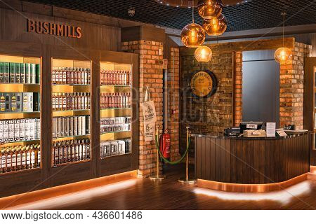 Bushmills, Northern Ireland, Aug 2019 Bushmills Whiskey On Illuminated Shelfs On A Display And Cash