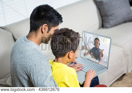 Biracial boy with father using laptop for video call, with elementary school pupil on screen. communication technology and online education, digital composite image.