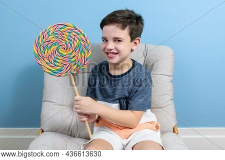 8 Year Old Child Holding A Big Colorful Lollipop, Smiling And Looking At The Camera.