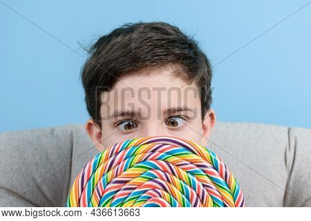 Closeu Of An 8 Year Old Child With A Fixed Gaze And Holding A Large Colorful Lollipop.