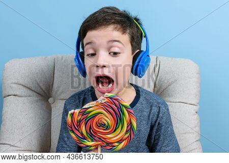 8 Year Old Brazilian Child, With Headphones, Holding A Colorful Lollipop And With His Mouth Open Rea