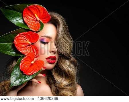 Beautiful white girl with red  flowers. Stunning girl with  Anthurium red. Closeup face of young beautiful blonde woman with a healthy clean skin. Pretty woman with bright makeup and long wavy hair.