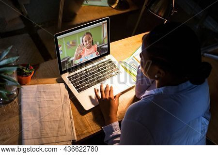 African american woman using laptop for video call, with waving elementary school pupil on screen. communication technology and online education, digital composite image.