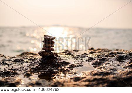 Pyramid Pebble On Stone With Sun Set On Sea Nature At Coast. Stack Zen With Ocean Bokeh Twilight Lan
