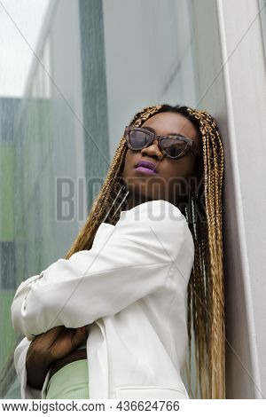 Empowered African American Young Woman Wearing Sunglasses Looking At Camera With A Daring Attitude.