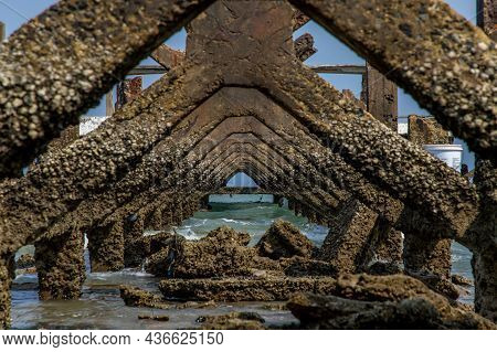 View Under At Broken Old Structure Remains Of Pier In The Sea. Small Wave Crashing Into The Textured