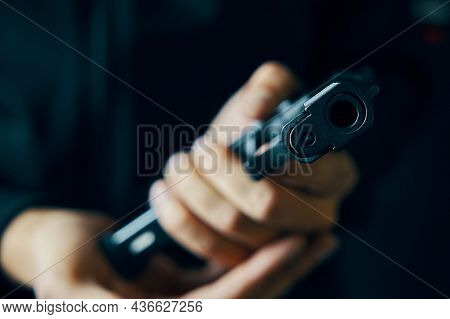 Muzzle Of Gun Close-up. Man Reloading Pistol. Weapon Ammunition. Firearms In Hand On Dark Background