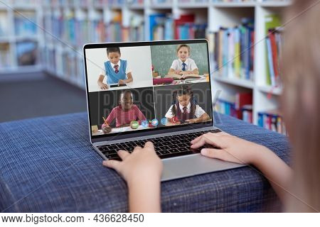 Caucasian girl using laptop for video call, with smiling diverse elementary school pupils on screen. communication technology and online education, digital composite image.