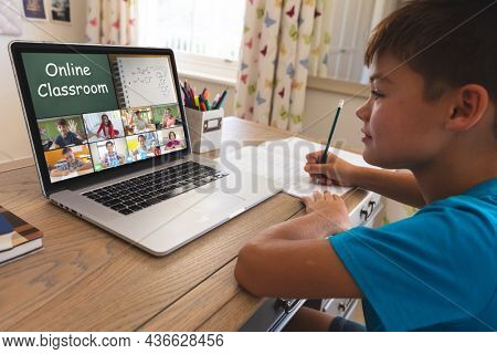 Smiling caucasian boy using laptop for video call, with diverse elementary school pupils on screen. communication technology and online education, digital composite image.
