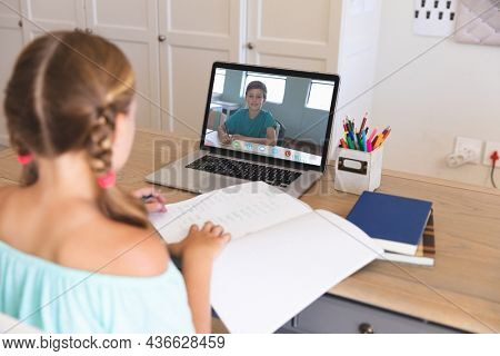 Caucasian girl using laptop for video call, with smiling elementary school pupil on screen. communication technology and online education, digital composite image.