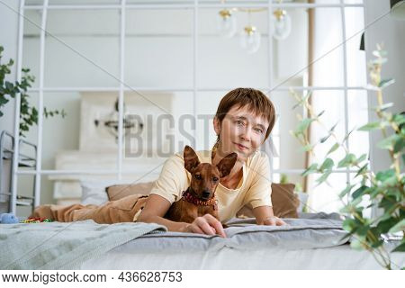 Cute Woman Lying On Her Stomach Relaxing In Bed With Her Beloved Dog. Morning Caresses In A Warm Com