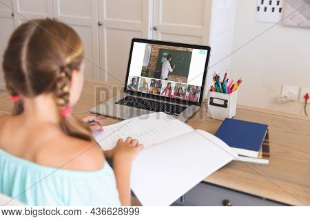 Caucasian girl using laptop for video call, with diverse elementary school pupils on screen. communication technology and online education, digital composite image.