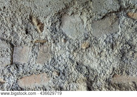 Ruined And Weathered Plaster On An Old Brick Wall. Texture And Pattern Of Damaged Brickwork.