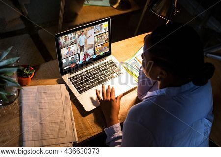 African american woman using laptop for video call, with diverse elementary school pupils on screen. communication technology and online education, digital composite image.